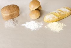 Different sorts of flour and loafs of bread on the paper background royalty free stock photo