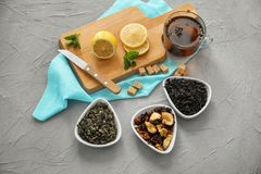 Different types of dry tea leaves and cup of aromatic beverage on table stock images