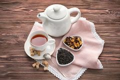 Different types of dry tea leaves and cup of aromatic beverage on wooden table stock photos