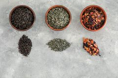 Different types of dry tea leaves on grey background stock photography
