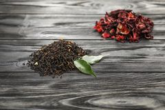 Different types of dry tea leaves on wooden background royalty free stock images