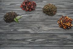 Different types of dry tea leaves on wooden background stock images