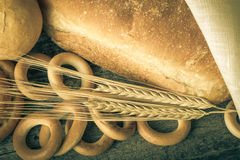 Different types of fresh bread and wheat ears on old wooden tabl Royalty Free Stock Photography