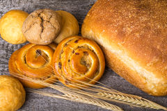 Different types of fresh bread and wheat ears on old wooden table Royalty Free Stock Photo