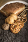 Different types of fresh bread and wheat ears on old wooden table Royalty Free Stock Photography