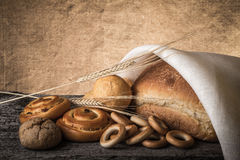 Different types of fresh bread and wheat ears on old wooden table Stock Image