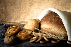 Different types of fresh bread and wheat spikes on old wooden ta Stock Photos