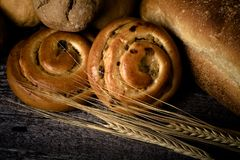 Different types of fresh bread and wheat spikes on old wooden ta Stock Images