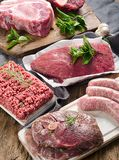 Different types of fresh raw meat on dark wooden background. Top view Royalty Free Stock Image