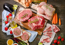 Different types of fresh raw meat with vegetables and herbs on w. Ooden table. View from above Royalty Free Stock Photo