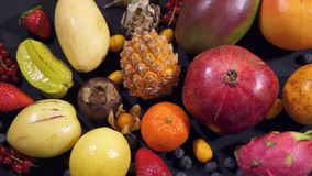 Different types of fruit spread out on a table on a black background. 4k stock footage