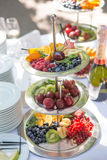Different types of fruits on three-storey plate Stock Photos
