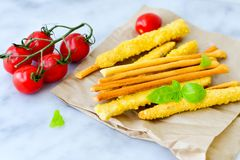 Grissini. Different types of grissini - tradition Italian breadsticks and mini san Marzano italian cherry tomatoes. Mediterranian lunch stock photos