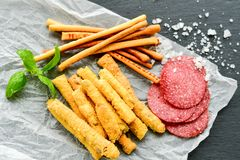 Grissini. Different types of grissini - tradition Italian breadsticks and salami. Mediterranian lunch stock image