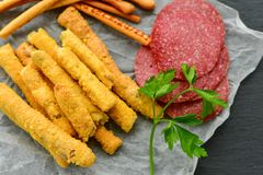 Grissini. Different types of grissini - tradition Italian breadsticks and salami. Mediterranian lunch stock photo