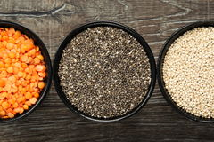 Different types of healthy grains in bowls on wooden background royalty free stock image