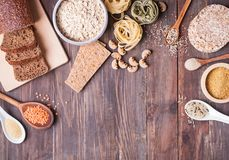 Different types of high carbohydrate food on the wooden table. Different types of high carbohydrate food. Flour, bread, dry pasta and lentils and other stock photo
