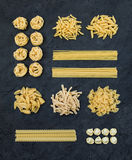 Different types of Italian uncooked pasta on black slate stone background, top view. Vertical Royalty Free Stock Image