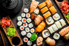 Different types of Japanese sushi, rolls and maki with sauce, wasabi and green tea in a teapot. On dark rustic background royalty free stock photo