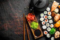 Different types of Japanese sushi, rolls and maki with sauce, wasabi and green tea in a teapot. On dark rustic background royalty free stock image