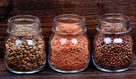 Different types of lentils in a jars on table Stock Images