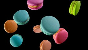 Different types of macaroons in motion falling on dark background stock image