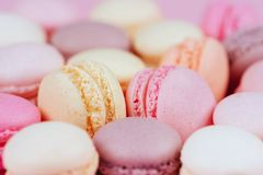 Different types of macaroons on pink background. stock photos