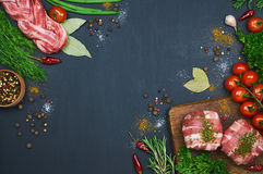Different types of meat. Fresh butcher cut meat assortment on dark background. Decorated with vegetables and spice. Top view. Close-up Royalty Free Stock Photo