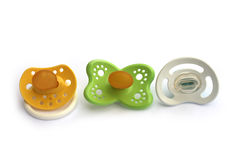 Different types of pacifiers. Three different types of pacifiers; a yellow with flat latex nipple, a green with oval latex nipple and a white silicon dummy Stock Photography
