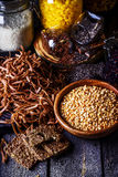 Different types of pasta, rice, peas,seeds of flax and chia on dark wooden table. Stock Photography