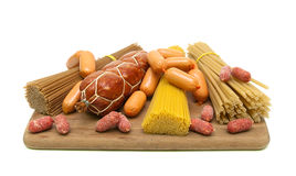 Different types of pasta and sausages on a cutting board. white Royalty Free Stock Photography