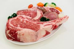 Different types of raw beef with fresh herbs and vegetables on the table for customer selection Stock Photo
