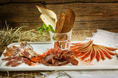 Different types of raw meat with herbs on a wooden background. Top view. Ham, fat with bread and greens and seasonings. Royalty Free Stock Photography