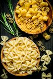 Different types of raw pasta in bowls with the rosemary. On black rustic background stock photography