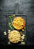 Different types of raw pasta in bowls with the rosemary. On black rustic background royalty free stock image