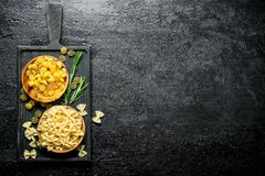 Different types of raw pasta in bowls with the rosemary. On black rustic background royalty free stock images