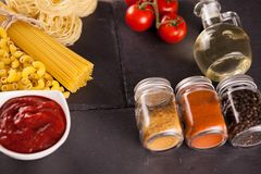 Different types of raw pasta next to sunflower oil, spices and a bowl with tomato souce. On dark vintage background stock photography
