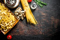 Different types of raw pasta with tomatoes, spices and mushrooms. On dark rustic background stock images