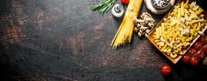 Different types of raw pasta with tomatoes, spices and mushrooms. On dark rustic background stock photos