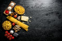 Different types of raw paste with Parmesan, mushrooms and tomatoes. On black rustic background stock photo