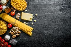 Different types of raw paste with Parmesan, mushrooms and tomatoes. On black rustic background royalty free stock photography