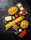 Different types of raw paste with Parmesan, mushrooms and tomatoes. On black rustic background stock photos