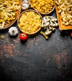 Different types of raw paste on a plate with garlic and mushrooms. On rustic background stock photo
