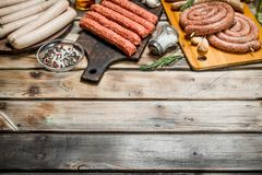 Different types of raw sausages with seasonings and herbs stock photo