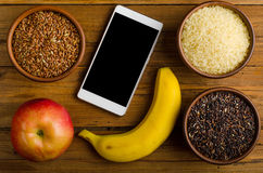 Different types of rice, smartphone, apple and banana on a woode Royalty Free Stock Photography