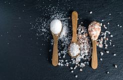 Different types of salt. Top view on three wooden spoons royalty free stock images