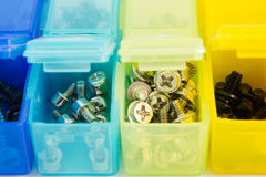 Different types of screws in small colored plastic containers. V Stock Images