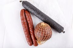 Different types of smoked salami sausages on white royalty free stock photo