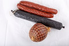 Different types of smoked salami sausages on white royalty free stock images