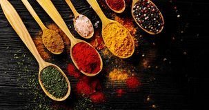 Different types of spices in spoons. From above view of different sort of colorful spices placed in spoons on wooden background royalty free stock image